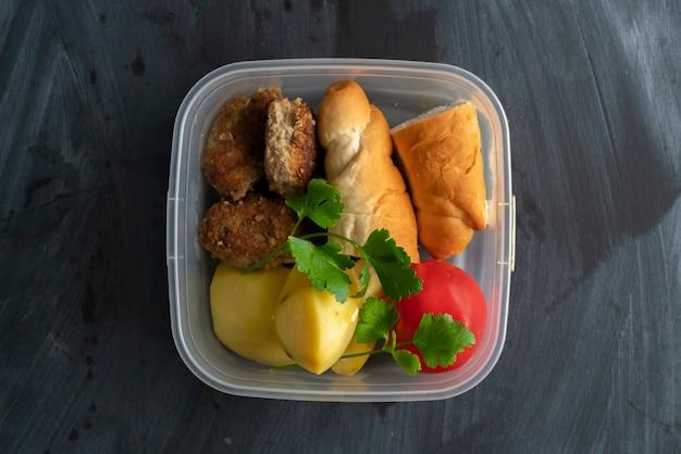 Un concetto di ora di pranzo, mangiare dal contenitore di plastica con carne e patate sui tavoli Foto Premium