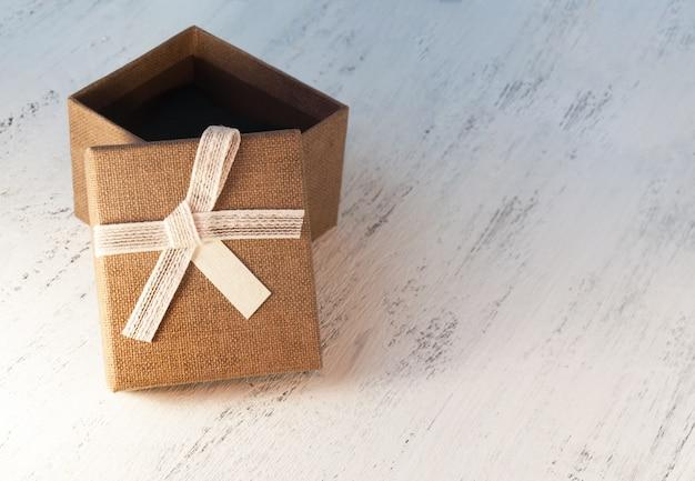 Un contenitore di regalo marrone e un nastro beige con un'etichetta su un fondo leggero. un regalo di natale tonificazione e sfocatura. Foto Premium