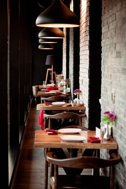 Un corridoio ristorante con piccoli tavoli da due persone Foto Gratuite