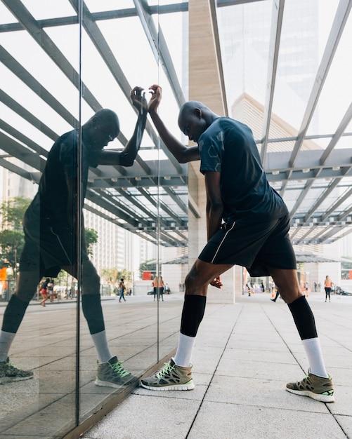 Un corridore maschio che allunga il suo muscolo in piedi davanti al vetro Foto Gratuite