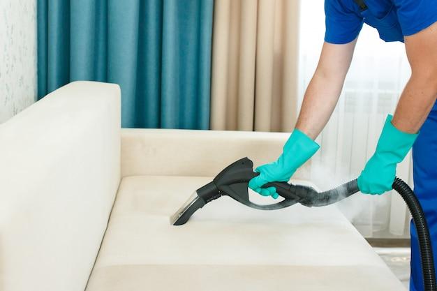 Un dipendente di un'impresa di pulizie fornisce un servizio di pulizia chimica e a vapore per il divano. pulitore a vapore Foto Premium