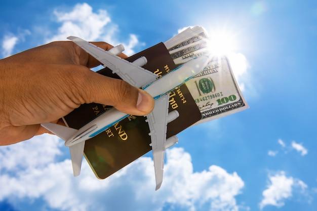 Un dollaro e un passaporto e l'aereo di un uomo su uno sfondo di cielo. Foto Premium