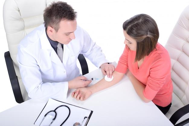 Un dottore maschio in camice da laboratorio controlla una ragazza. Foto Premium