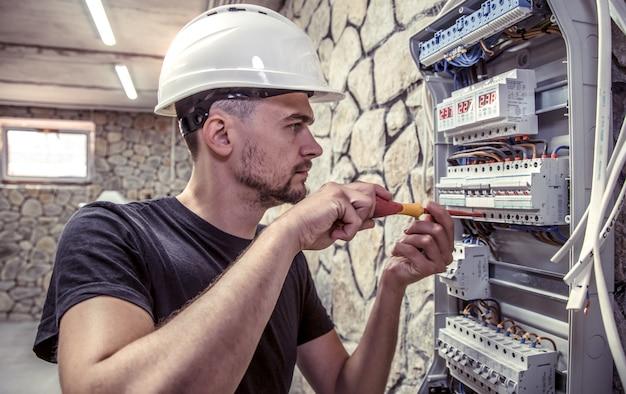 Un elettricista maschio lavora in un centralino con un cavo di collegamento elettrico Foto Gratuite