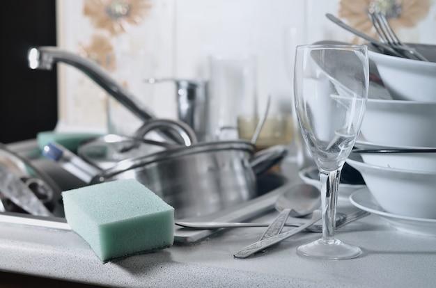 Un enorme mucchio di piatti non lavati nel lavandino della cucina e sul bancone Foto Premium