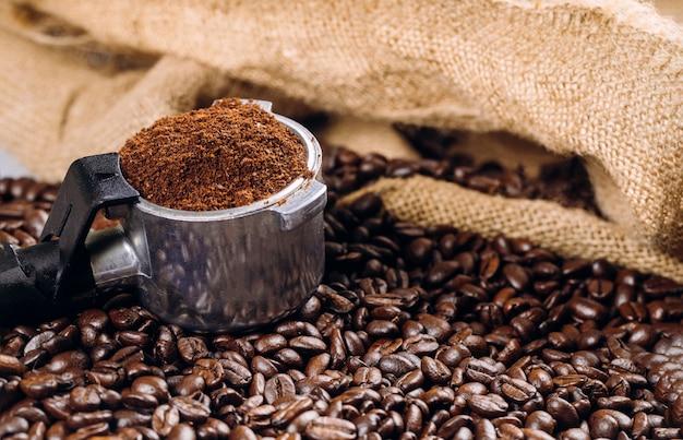Un espresso pieno di vista dall'alto del portafiltro con chicchi di caffè Foto Premium