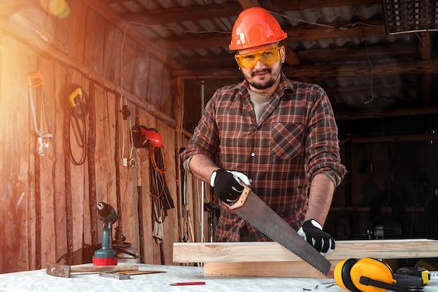 Un falegname uomo taglia una trave di legno usando una sega a mano, mani maschili con un primo piano sega. Foto Premium