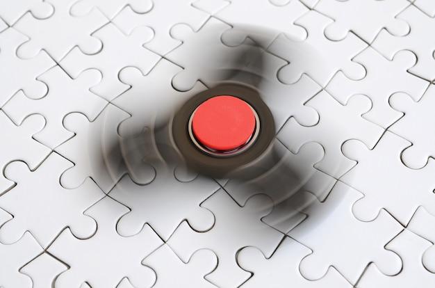 Un filatore di legno gira su una priorità bassa bianca del puzzle Foto Premium