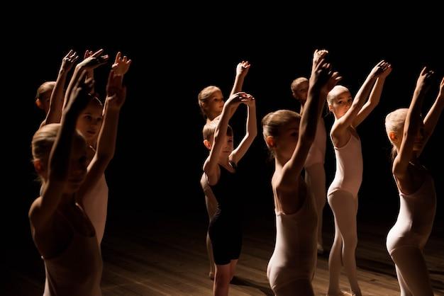 Un folto gruppo di bambini che provano e ballano il balletto Foto Premium