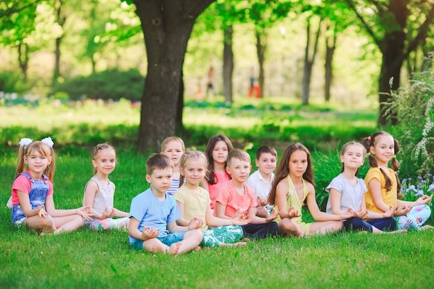 Un folto gruppo di bambini impegnati nello yoga nel parco seduto sull'erba. Foto Premium