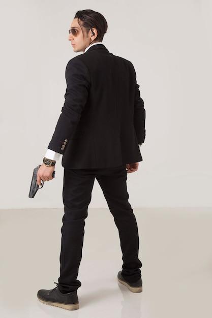 Un gangster che fuma con un'arma Foto Gratuite