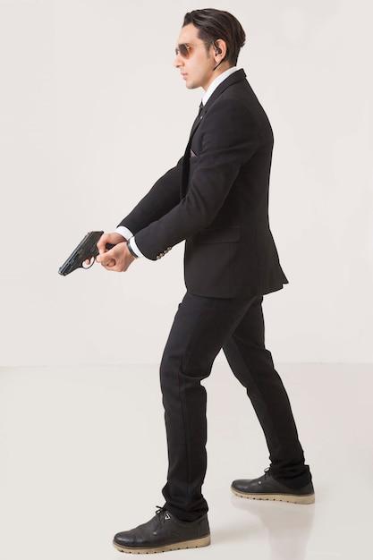 Un gangster in business suite esibendosi con un'arma su sfondo bianco Foto Gratuite