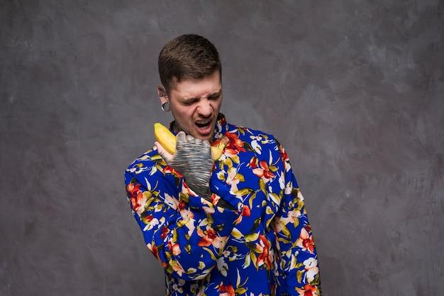 Un giovane arrabbiato con tatuato sulla sua mano urlando sul telefono banana contro il muro grigio Foto Gratuite