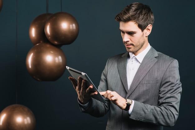 Un giovane attraente utilizzando la tavoletta digitale con pendente in metallo moderno Foto Gratuite