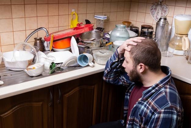 Un giovane barbuto si siede per terra ed è scioccato dalla quantità di piatti sporchi che giacciono nel lavello della cucina per essere lavati. Foto Premium