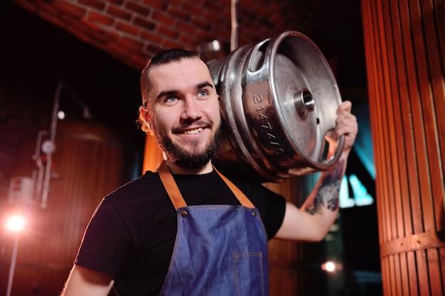 Un giovane bel birraio maschio detiene una botte di ferro con birra sullo sfondo del birrificio e serbatoi di birra Foto Premium