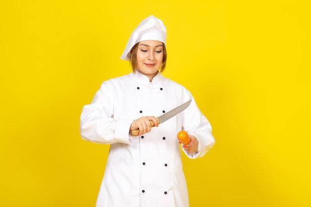 Un giovane cuoco femminile di vista frontale nel vestito bianco del cuoco e nel carrott sorridente del taglio della lama della holding della protezione bianca sul giallo Foto Gratuite