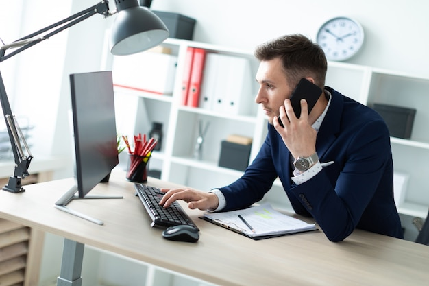 Un giovane è in piedi vicino a un tavolo in ufficio, parla al telefono e digita il testo sulla tastiera. Foto Premium