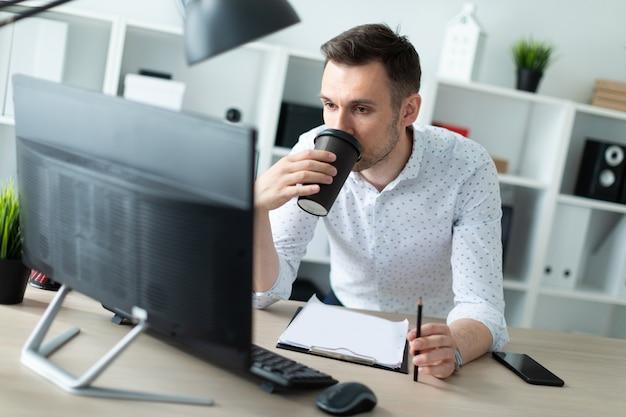 Un giovane è in piedi vicino a un tavolo in ufficio, tiene una matita in mano e beve il caffè. un giovane lavora con documenti e un computer. Foto Premium