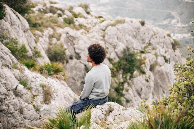 Un giovane escursionista maschio africano che si siede sulla montagna rocciosa Foto Gratuite