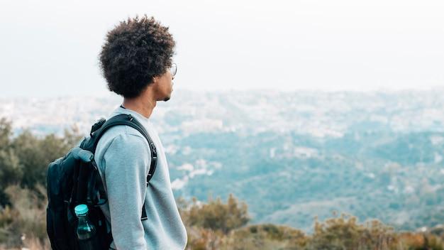 Un giovane escursionista maschio africano con il suo zaino guardando vista Foto Gratuite