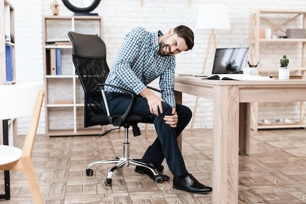Un giovane ha un dolore alla gamba. si massaggia Foto Premium