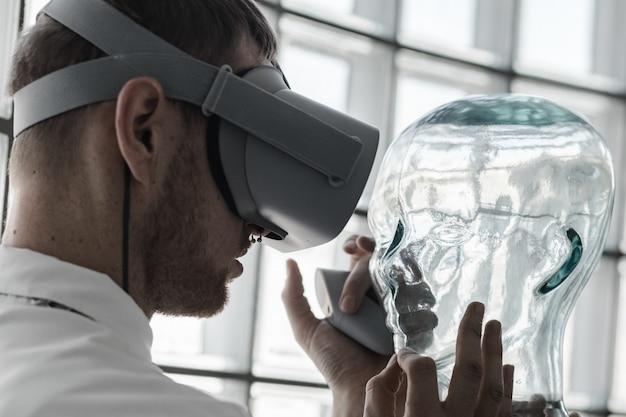 Un giovane medico che indossa occhiali vr esaminando un manichino nella simulazione vr - futuro concetto di tecnologia Foto Gratuite