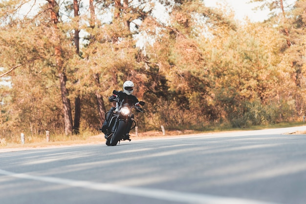 Un giovane ragazzo in un casco sta cavalcando su una strada forestale Foto Premium