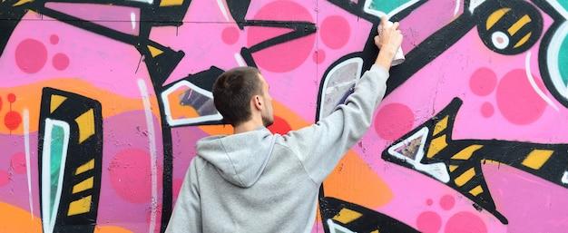 Un giovane ragazzo in una felpa grigia dipinge graffiti in rosa e verde c Foto Premium