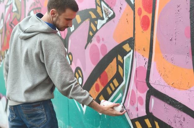 Un giovane ragazzo in una felpa grigia dipinge graffiti in rosa e verde Foto Premium