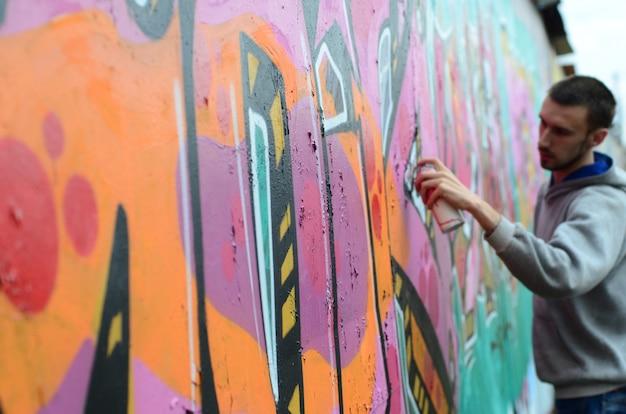 Un giovane ragazzo in una felpa grigia dipinge graffiti Foto Premium