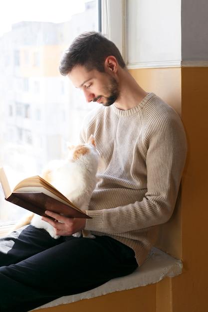 Un giovane si siede su un davanzale e legge un libro. accanto all'uomo siede un gatto bianco con macchie rosse. un uomo indossa un maglione beige. Foto Premium