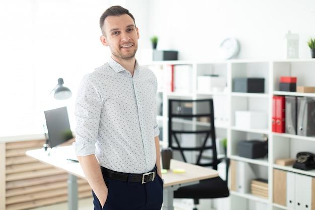Un giovane si trova vicino a un tavolo in ufficio, con le mani in tasca. Foto Premium