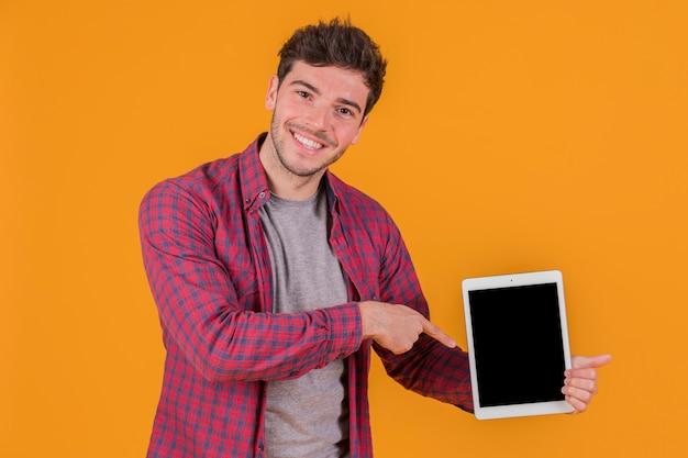 Un giovane sorridente che punta il dito contro la tavoletta digitale contro uno sfondo arancione Foto Gratuite
