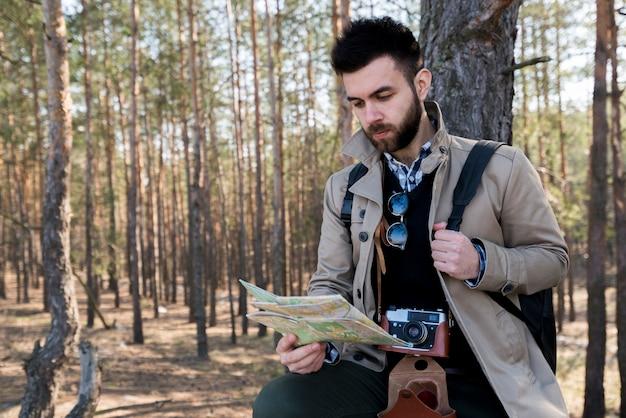 Un giovane turista maschio che legge la mappa nella foresta Foto Gratuite