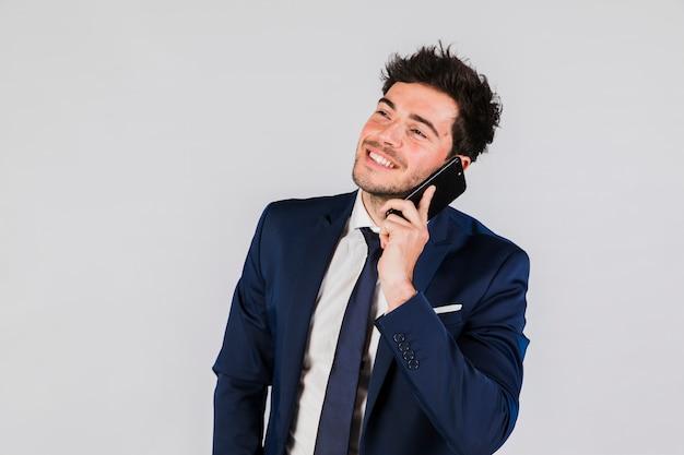 Un giovane uomo d'affari che parla sul telefono cellulare contro fondo grigio Foto Gratuite