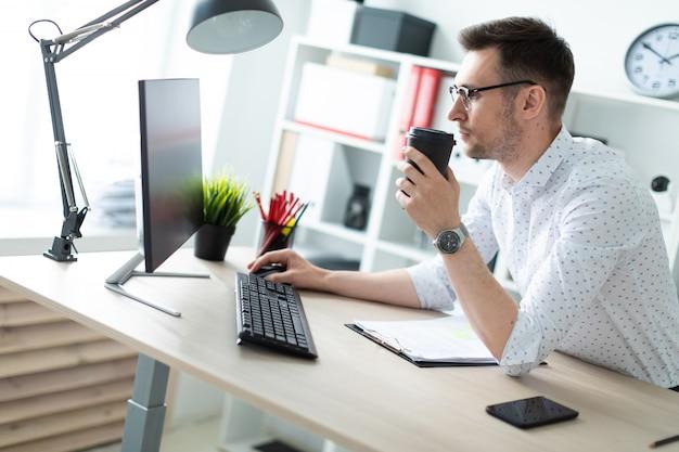 Un giovane uomo in occhiali si trova vicino a un tavolo in ufficio Foto Premium