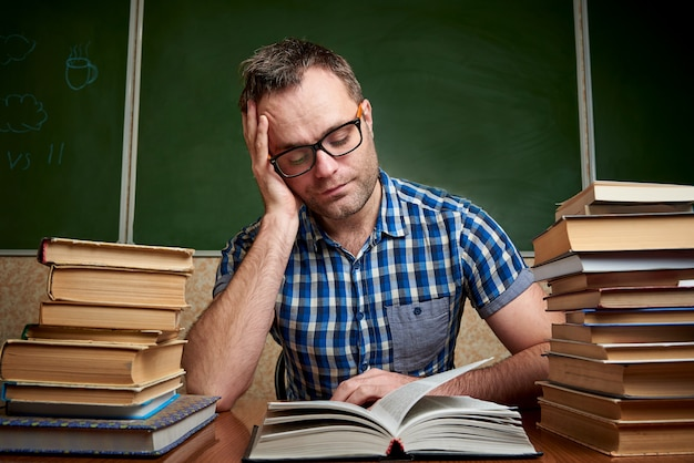 Un giovane uomo legge un libro a un tavolo con pile di libri. Foto Premium