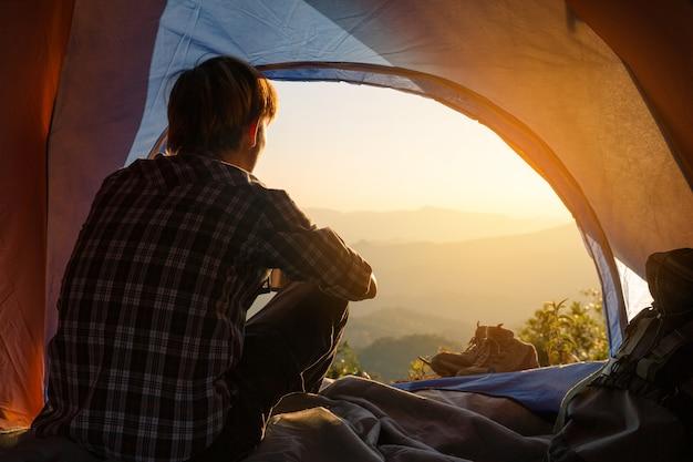 Un giovane uomo seduto nella tenda con la tazza di caffè in mano Foto Gratuite