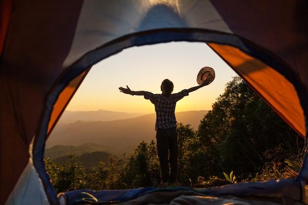 Un giovane uomo seduto nella tenda con scattare foto con un telefono cellulare Foto Gratuite