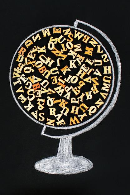 Un globo contenente lettere di legno dell'alfabeto inglese Foto Premium