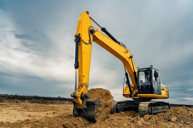 Un grande escavatore da cantiere di colore giallo in cantiere in una cava per l'estrazione. immagine industriale Foto Premium