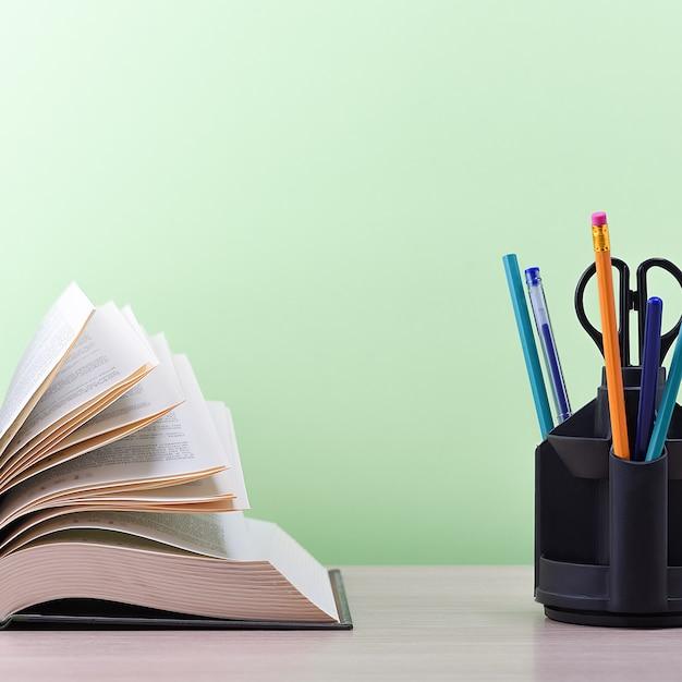 Un grande libro spesso con le pagine aperte come un ventaglio e un supporto con penne, matite e forbici sul tavolo su uno sfondo verde. Foto Premium
