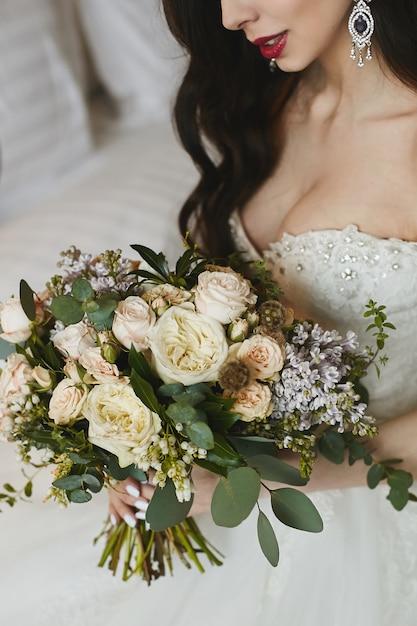 Un grande mazzo di fiori nelle mani della bellissima modella bruna dai grossi seni con grandi orecchini di lusso con diamanti nell'abito da sposa alla moda Foto Premium