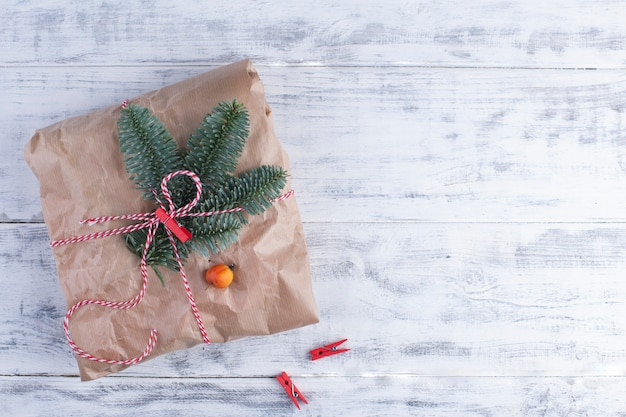 Un grande regalo in carta grigia legato con una corda, su un blu di legno Foto Premium