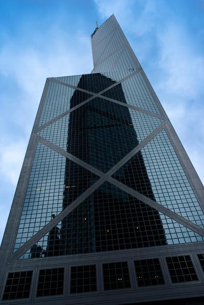 Un grattacielo alto in una facciata di vetro con il riflesso di un altro grattacielo a hong kong Foto Gratuite
