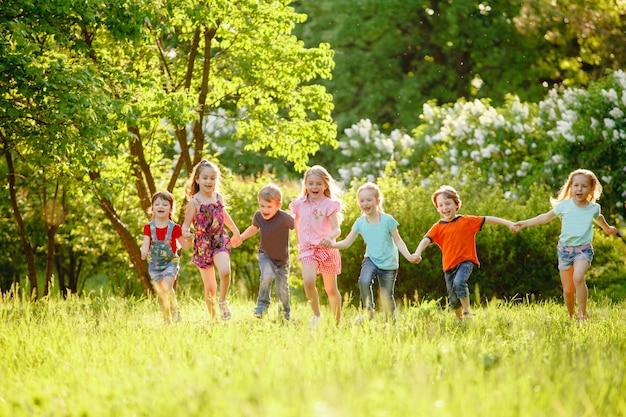 Un gruppo di bambini che giocano e corrono nel parco su un gozon verde. Foto Premium