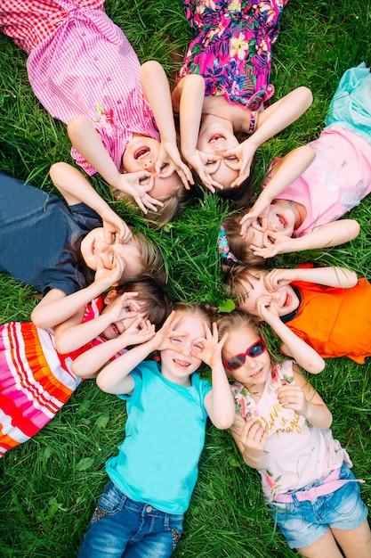 Un gruppo di bambini che si trovano sull'erba verde nel parco. Foto Premium