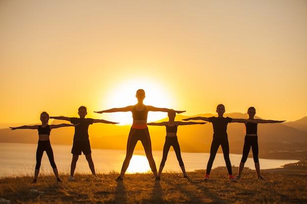 Un gruppo di bambini è impegnato nello yoga con un istruttore sull'oceano. Foto Premium