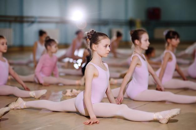 Un gruppo di bambini in una scuola di balletto o in una sezione di ginnastica sui tappeti carimat eseguono esercizi Foto Premium